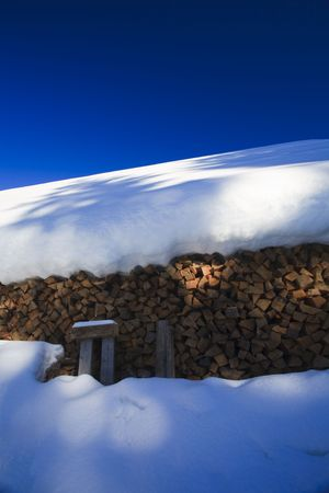 Firewood covered in winter snow in Austria photo