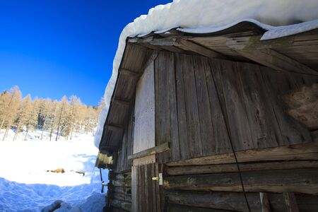 Old barn in winter in the mountains on a sunny day photo