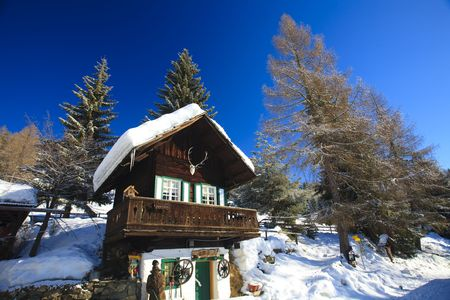 Snow covered cabin in the alps in winter with blue sky Stock Photo - 5932801