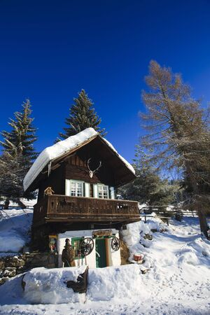 Snow covered cabin in the alps in winter with blue sky Stock Photo - 5932798