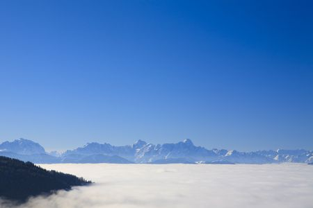 High in the mountains of the Alps in Austria above the clouds with a blue sky photo