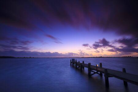 Einen ruhigen Sonnenuntergang über einen See in den Niederlanden