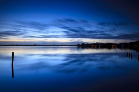 Ruhige Sonnenaufgang über einen See mit Wolken Reflexion im Wasser