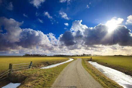Sunrise über eine flache Feld in den Niederlanden mit einem hellen Skie und Wolken