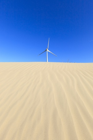 Wind turbines in the desert with sand dunes
