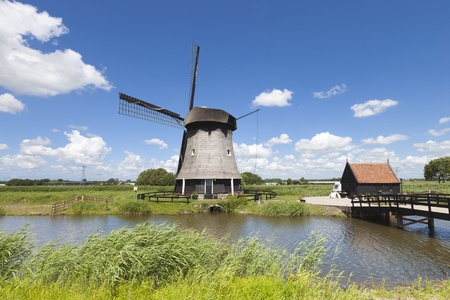 Dutch windmill in a fresh green field in summer with a blue sky photo