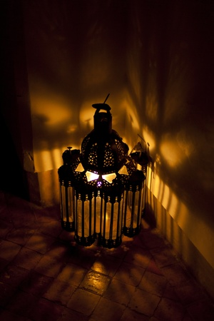 Bright Arabian lantern in a dark room photo