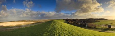 Grünes Feld mit schönen Himmel am Meer