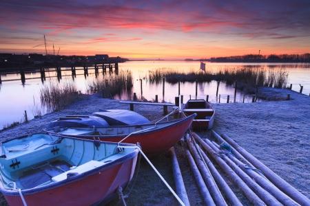 Schöner Sonnenuntergang mit Booten an der Küste Standard-Bild