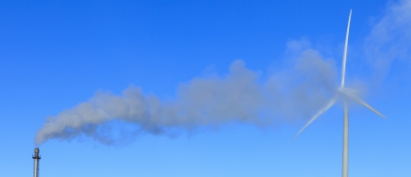 Wind turbine in the smoke of a polluting chimny photo