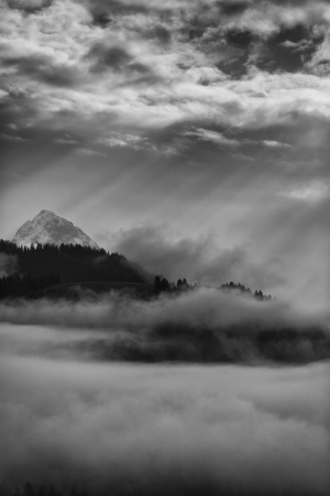 mountains with snow and storm clouds in black and white photo