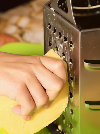 Hand grate cheese to cooking pizza photo