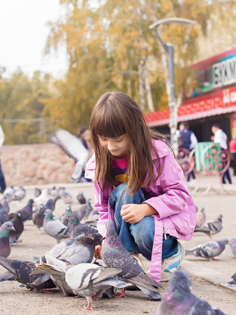 Small caucasian girl feeding pigeons photo