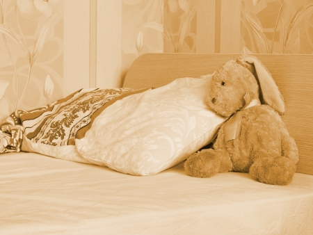 Borred rabbit toy lie on the bed awaiting child Imagens