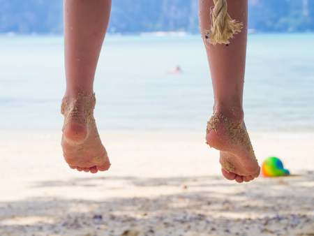 Legs of  caucasian girl, child, kid  on swing at the trpoical beach photo
