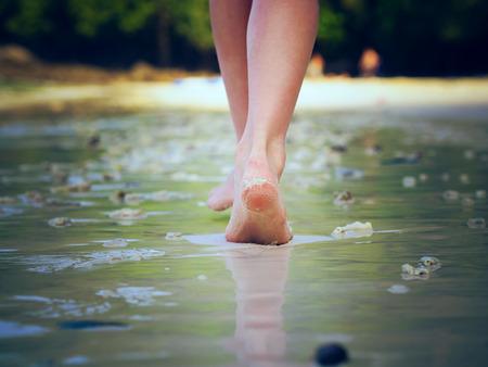 solos: Chica caminando en la playa de la arena dejando huellas