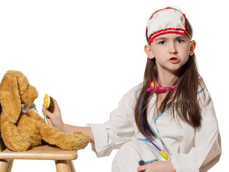 glands: Portrait of funny little caucasian girl in medical costume inspecting glands of rabbit toy isolated on white