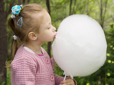 Young caucasian little girl eating big white cotton candy in the park outdoor photo