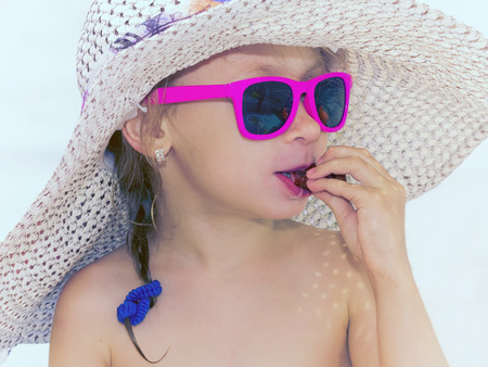 Little glamour girl in pink glasses eating sausage on the beach outdoor photo