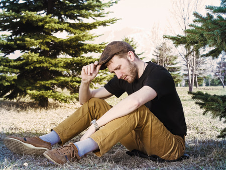 reflects: Young caucasian man reflects and sitting in meadow between firs at spring Stock Photo