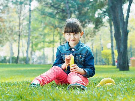 Portrait of nice caucasian girl kid clean fresh banana in summer outdoors photo