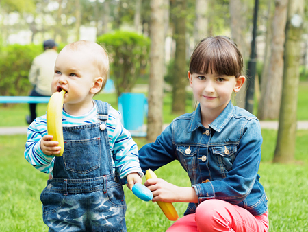 Portrait of nice caucasian brother with banana and sister walking at summer park outdoors photo