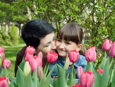 Portrait of nice happy caucasian family between tulips flowers at summer park outdoors photo