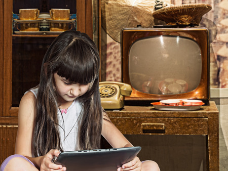 Caucasian child kid girl sister in old rarity home with tablet pc photo