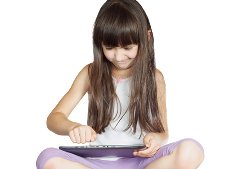 Caucasian angry child kid girl sister sitting on the bed with tablet pc isolated on white photo