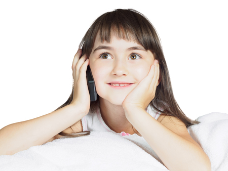 Caucasian child kid girl sister lying on the bed with mobile phone isolated on white photo