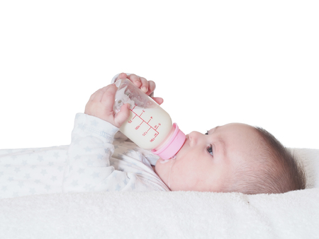 Caucasian baby boy four months drinking milk from the bottle isolated