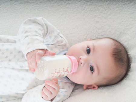 Caucasian baby boy four months drinking milk from the bottle at home photo