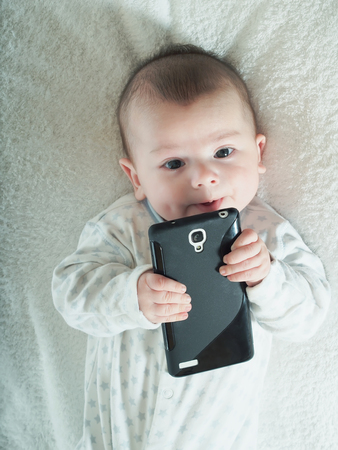 Funny small baby boy holding smartphone in bed photo