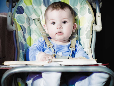 chear: Small caucasian baby sitting in chear with notepad
