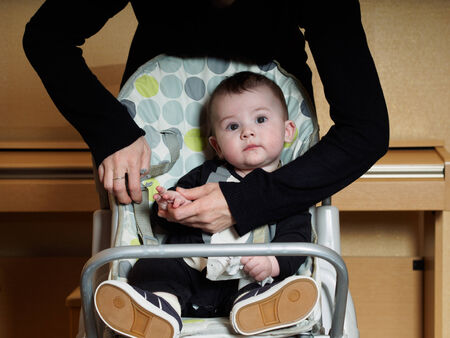 chear: Small caucasian baby in smoking sitting in child chear