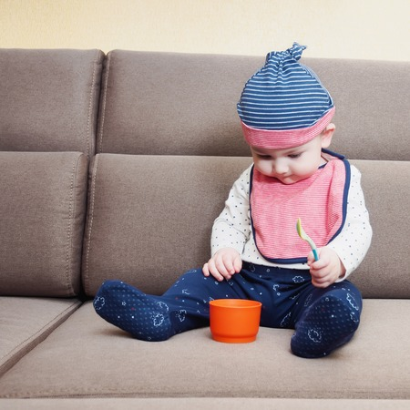 Caucasian baby boy weared bib sitting on brown sofa at home