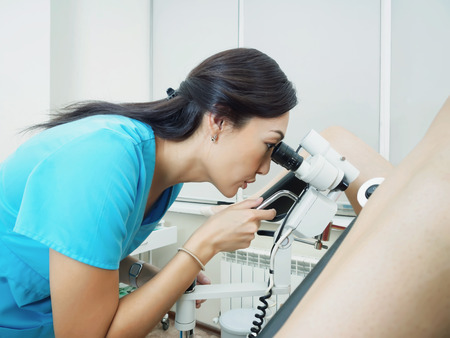 Asian woman gynecologist examining patient in hospital using a colposcope Stock Photo