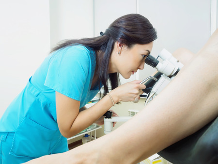 gynecologist: Asian woman gynecologist examining patient in hospital using a colposcope Stock Photo