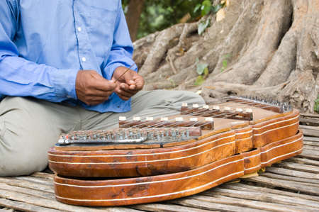 Close-up of a Cambodian musician playing a traditional khim musical instrument  A hammered dulcimer, or zither, style of instrument it has brass strings struck with bamboo hammers