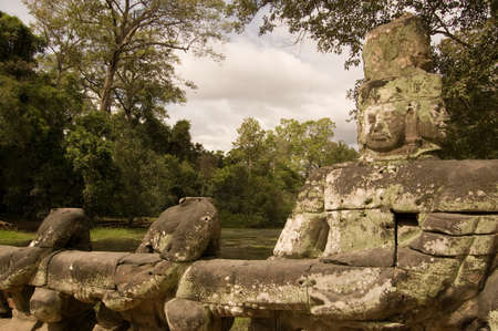 churning: Statue of Vishnu pulling on the Naga serpent in the Churning of the Ocean of Milk legend   Causeway to the ancient Khmer Preah Khan Temple, Angkor, Cambodia
