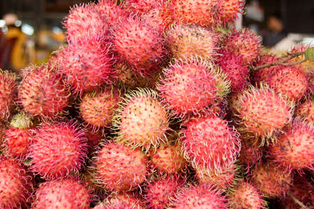 A heap of ripe rambutan fruit - latin name  nephelium lappaceum -  on a market stall in Cambodia