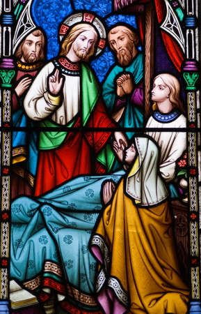 Victorian stained glass window showing Jesus Christ healing a sick young man.