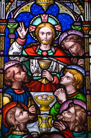 A Victorian stained glass window depicting the Last Supper, or Holy Eucharist.  Jesus Christ holding the Holy Grail with his disciples dining on bread and wine.