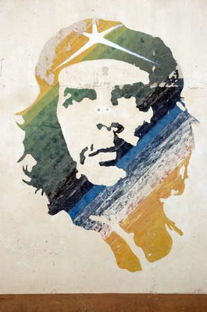 A wall painted with a colourful mural of the Cuban revolutionary leader Che Guevara   The image over looks a car park in Old Havana