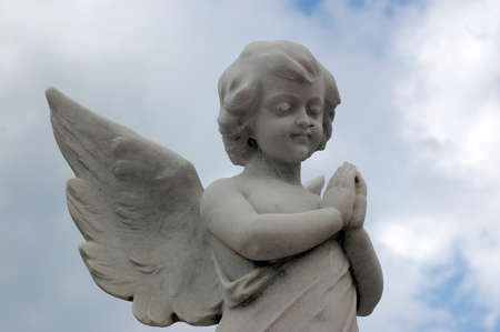 angel cemetery: Stone carved statue of a cherub praying above a nineteenth century grave  Stock Photo