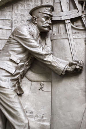 Detail of the bronze relief showing engineers on the Titanic continuing to operate equipment while the ship sinks   Memorial on public display since 1914 in Southampton, Hampshire