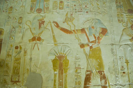 Ancient Egyptian bas relief showing the Ibis headed god Thoth praising god of the dead Osiris   Wall at Abydos Temple, el Balyana, Egypt  Ancient carving on public display over 2000 years