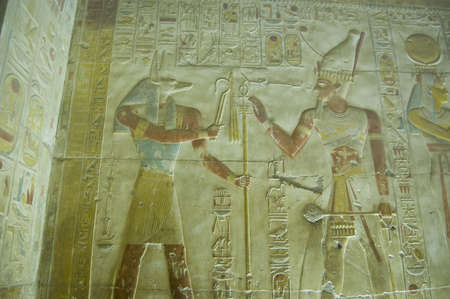 Ancient Egyptian bas relief showing the jackal headed god Anubis being worshipped by Pharaoh Seti I   Ancient carving at Abydos Temple, el Balyana, Egypt  On public display over 1000 years