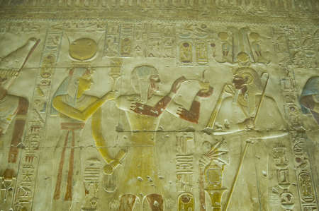 Ancient Egyptian bas relief showing Pharaoh Seti I offering incense to the god Osiris with Hathor standing behind him    Abydos Temple, Egypt    Ancient carving, on display over 1000 years  Editorial