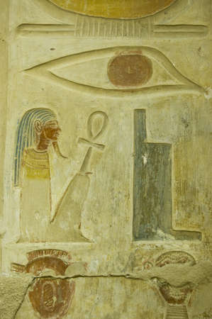 Ancient Egyptian hieroglyphs carved on a wall of Abydos Temple near el Balyana, Egypt   An eye, throne, squatting pharaoh and two heads    Ancient carving, on public display over 1000 years  Stock Photo - 15461278